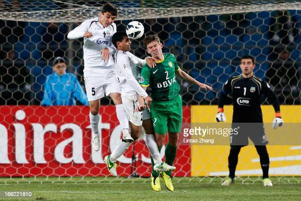 Egor Krimets of Beijing Guoan competes for an aerial ball with Dilshod Juraev and Akmal Shorakhmedov of Bunyodkor during the AFC Champions League...