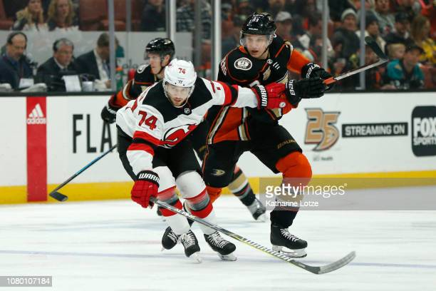 Egor Yakovlev of the New Jersey Devils and Jakob Silfverberg of the Anaheim Ducks fight for control of the puck at Honda Center on December 09 2018...