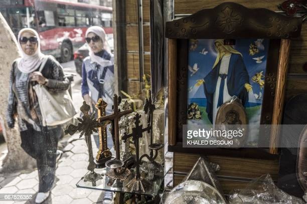 Egypian women walk past a church's paraphernalia shop displaying crucifixes and images of Christ and Coptic Orthodox religious figures in Cairo's...