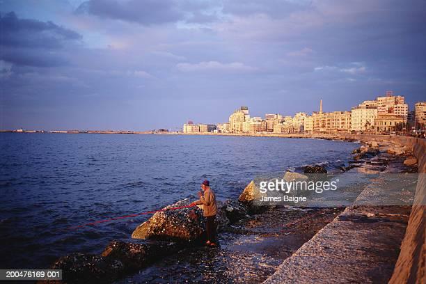Egypt, Alexandria, senior man fishing, sunset