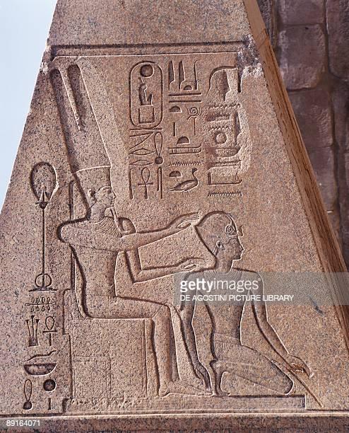Egypt Ancient Thebes Luxor Karnak Great Temple of Amon Pink granite obelisk Relief of Amon protecting Hatshepsut as pharaoh