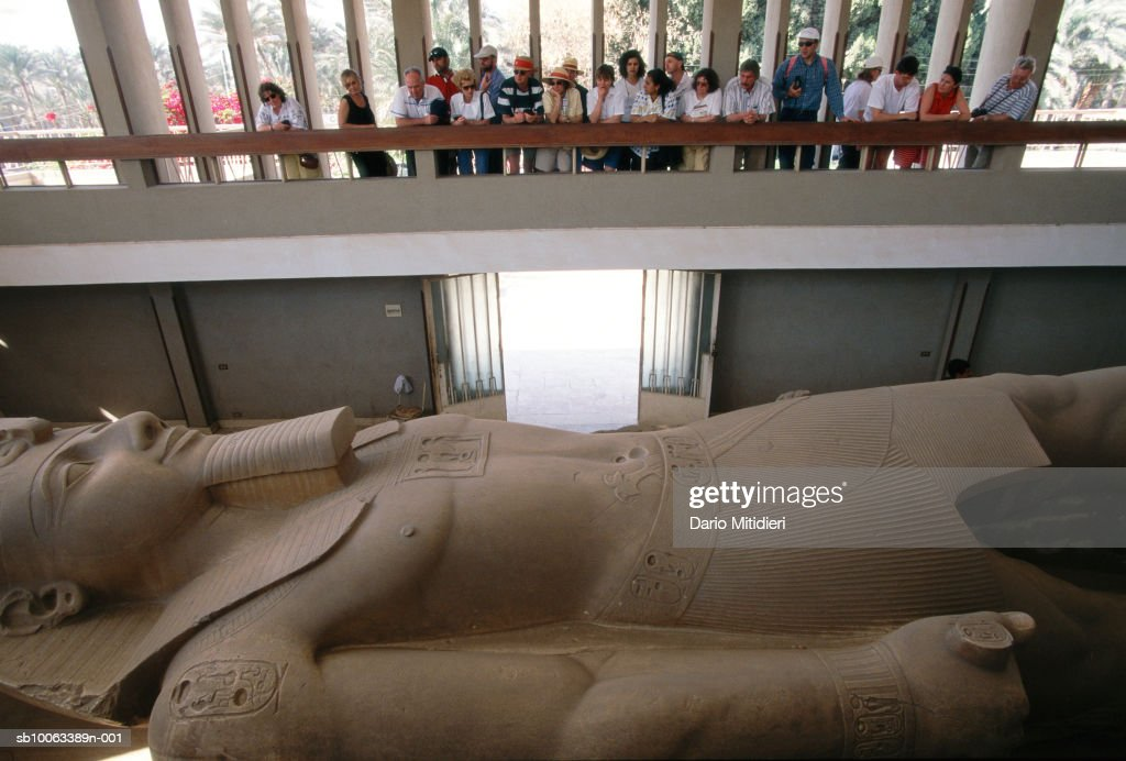 Group of tourists looking at huge sculpture of pharaoh
