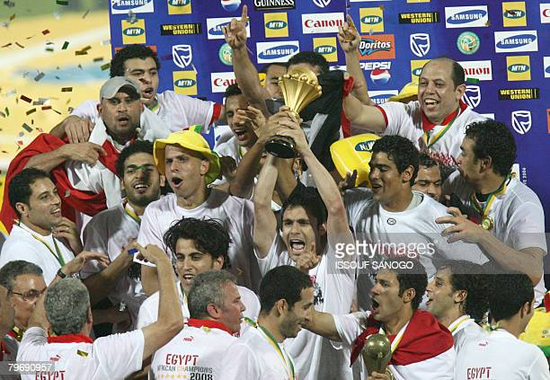 Egypt national football team captain Ahmed Hassan flanked by his teammates holds the cup after defeating Cameroon 10 on February 10 2008 in Accra...