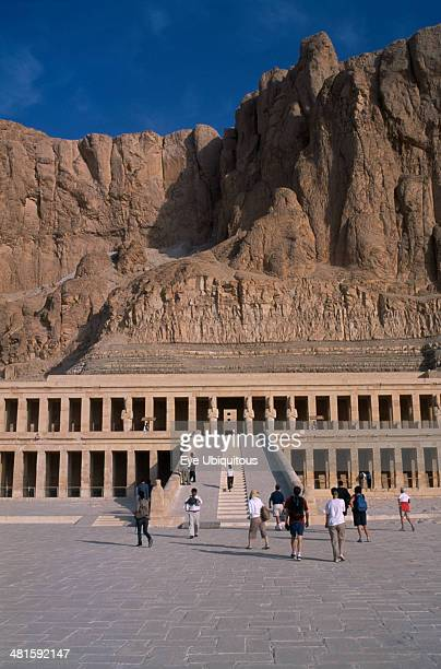 Egypt Nile Valley Thebes Deir elBahri Hatshepsut Mortuary Temple Visitors walking towards ramped entrance with limestone cliffs behind