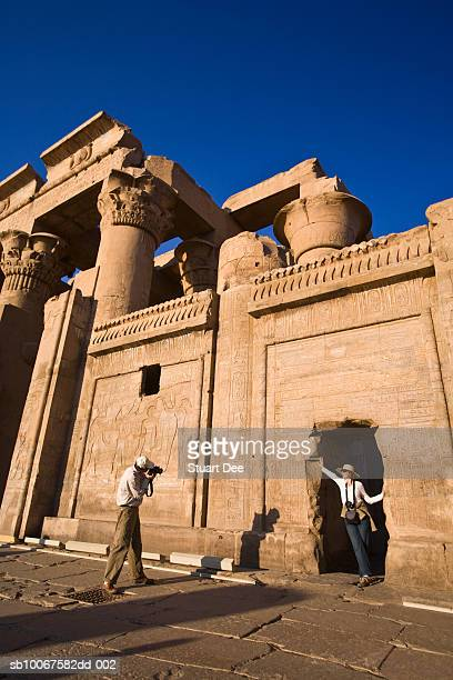 egypt, north of aswan, kom ombo, temple of kom ombo, man taking photograph of woman at temple ruins - aswan stock pictures, royalty-free photos & images