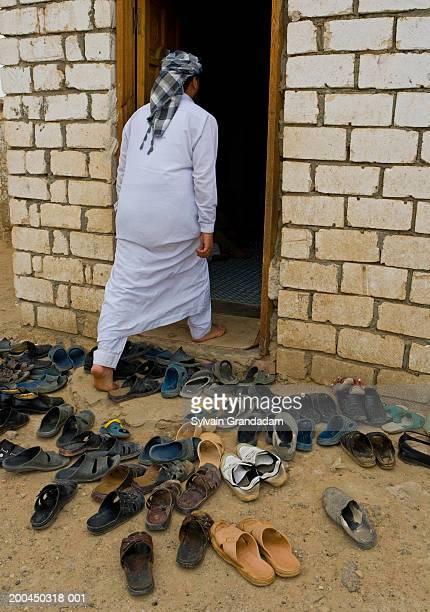 Egypt, Oasis of Bahariya, man entering mosque, shoes outside