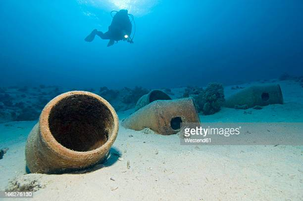 Egypt, Red Sea, Scuba diver and amphoras on ocean bed