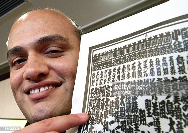 Egyptian Abdelrahman Ahmed Shaalan who goes by the ring name of Osunaarashi smiles as he shows a ranking list after being promoted to sumo's elite...