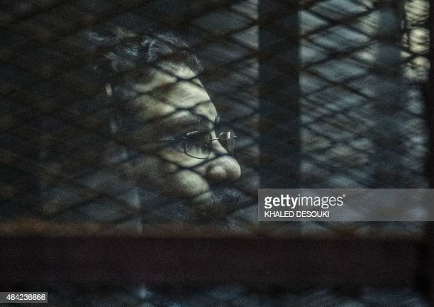 Egyptian activist Alaa Abdel Fattah stands behind bars with fellow defendants during their verdict at a police institute in Cairo's Tora prison on...