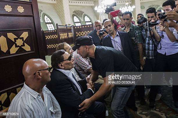 Egyptian actor Ahmed alSakaa shakes hands with veteran actor Adel Imam during the funeral of Egyptian film star Nur alSharif on August 12 at a mosque...