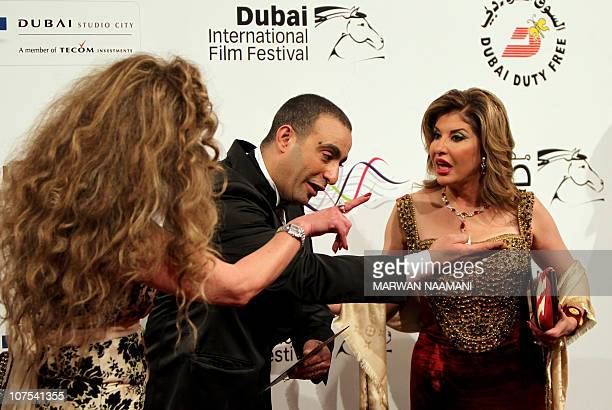 Egyptian actor Ahmed alSaqa gestures to Egyptian TV presenter Hala Serhan and Cairobased Syrian actress Raghda upon their arrival to attend the...