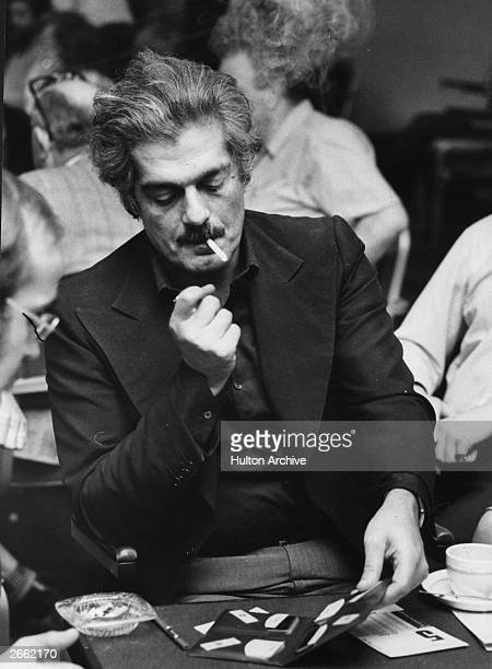 Egyptian actor Omar Sharif enjoying his other favourite occupation playing the card game Bridge He is concentrating on lighting his cigarette...
