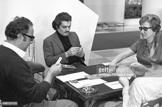 Egyptian actor Omar Sharif known for being a great bridge player playing cards with three people in the foyer of a theatre 1968