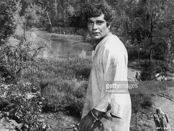 Egyptian actor Omar Sharif wearing a torn shirt and wrist manacles in a still from director Henry Levin's film 'Ghengis Khan'