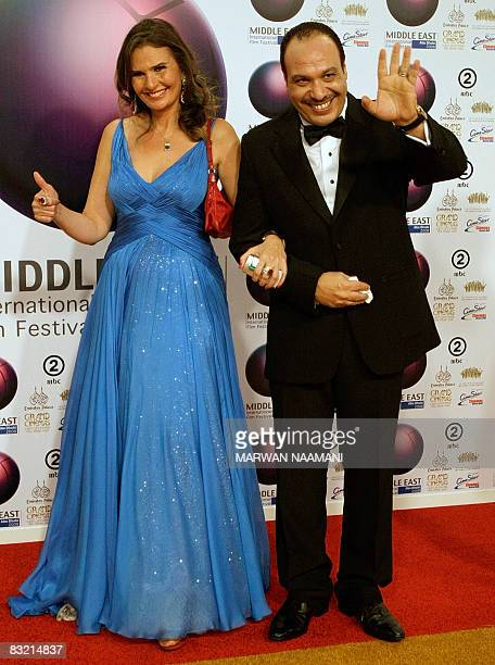 Egyptian actress Yusra gestures to journalists as she poses for a picture with actor Khaled Saleh at the opening ceremony of the Middle East...