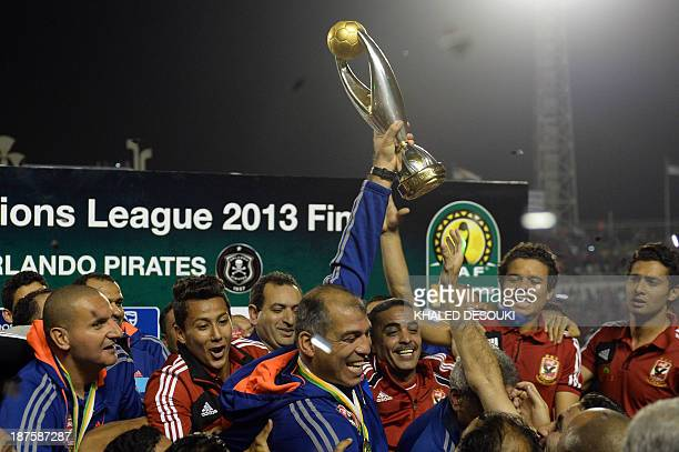 Egyptian alAhly coach Mohamed Youssef holds up the African Champions League trophy in Cairo on November 10 after defeating Orlando Pirates of South...