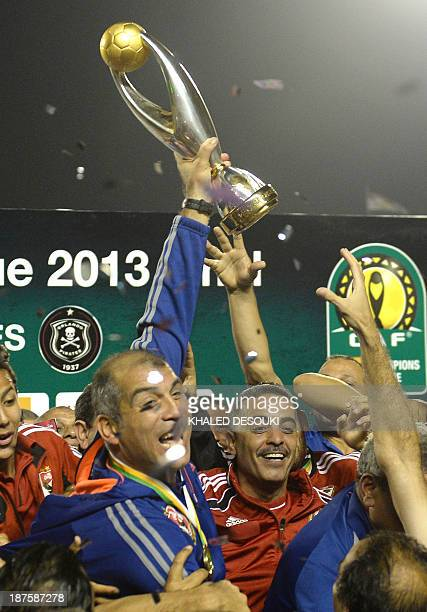 Egyptian AlAhly coach Mohamed Youssef holds up the winners trophy on November 10 as AlAhly won an eighth African Champions League when they beat...