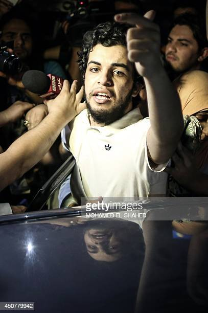 Egyptian AlJazeera journalist Abdullah Elshamy who has been on hunger strike gestures as he speaks to the media outside a police station in Cairo's...