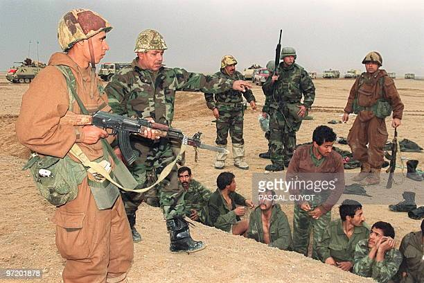 Egyptian and US soldiers guard Iraqi POWs 25 February 1991 in the Kuwaiti desert on the second day of the allied ground offensive against Iraqi army