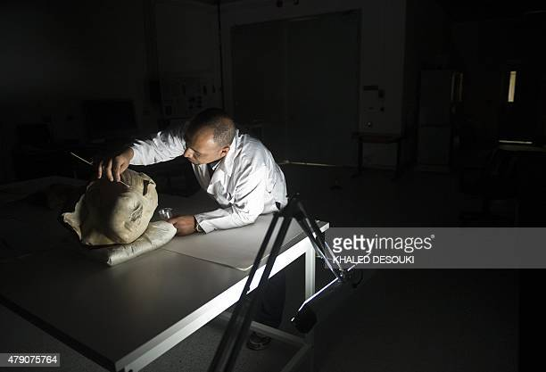 Egyptian archaeologist Basem Gehad cleans a pharaoh's head at part of the Grand Egyptian Museum still under construction near the Giza pyramids in...