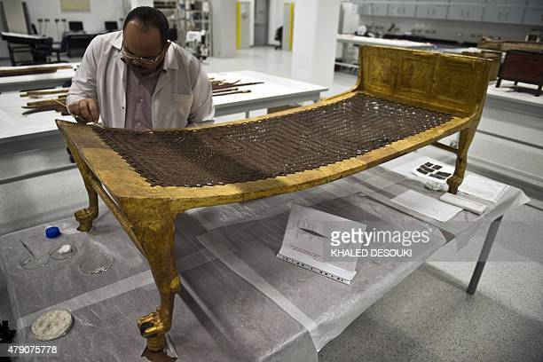 Egyptian archaeologist Medhat Abdallah cleans a goldplated bed from Tutankhamen's treasures at the new Grand Egyptian Museum near the Giza pyramids...