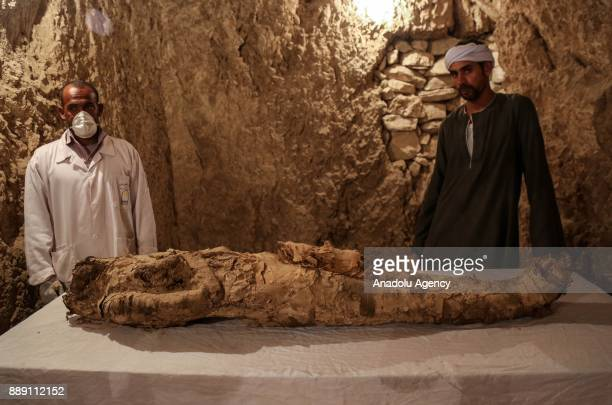 Egyptian archaeologists are seen near an ancient mummified body that belongs to the 18th Dynasty pharaohs in Dra Abu elNaga district of Luxor Egypt...