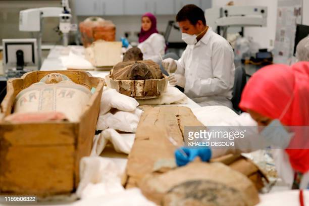 Egyptian archaeologists restore the coffin and mummy of King Tutankhamun at the conservation center in the Grand Egyptian Museum in Cairo on August...