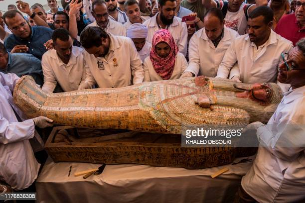 Egyptian archeologist open a wooden coffin belonging to a man in front Hatshepsut Temple at Valley of the Kings in Luxor on October 19 2019 Egypt...