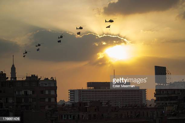 Egyptian army helicopters carrying flags circle Tahrir square on the evening of the 1st of July 2013. Each flag represents a different division of...