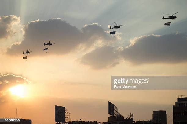 CONTENT] Egyptian army helicopters carrying flags circle Tahrir square on the evening of the 1st of July 2013 Each flag represents a different...