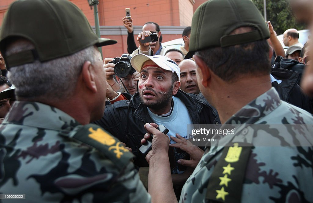 Egyptian army officers ask for patience from a protester in