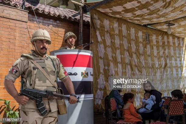 Egyptian army soldiers stand guard outside a polling station during the third day of a referendum on constitutional amendments in Cairo on April 22...
