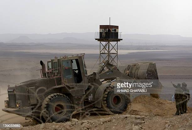 Egyptian border guards observe from a watch tower as a bulldozer moves dirt at the construction site of a border fence along Israel's border with...