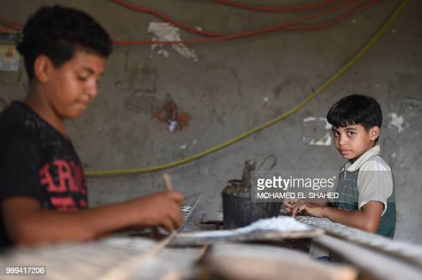 Egyptian boy Abbas Ali looks on as he works at a shop specialised in seashell wood inlays in the Saqyat alManqadi village in the Egyptian Nile Delta...