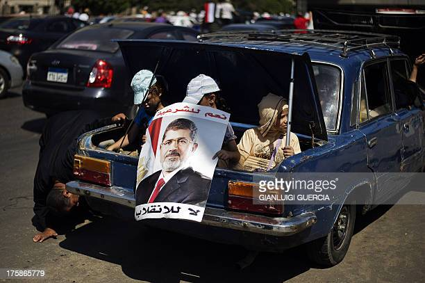 Egyptian children hold a portrait of ousted president Mohamed Morsi as they sit in a trunk of a car during a demonstration in support of Morsi in...