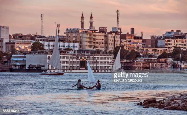 Egyptian children sit on a surfboard with an improvised sail in the Nile river in the southern city of Aswan some 920 kilometres away from the...