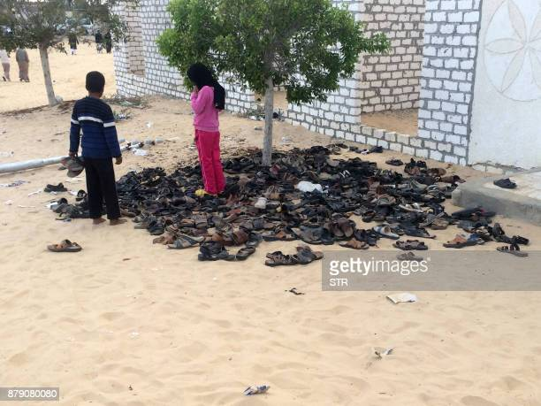 Egyptian children stand near a pile of footwear belonging to the victims of the attack that targeted the Rawda mosque near North Sinai provincial...