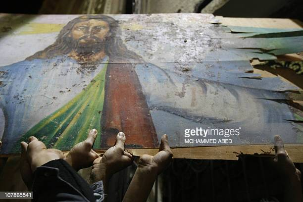 Egyptian Christians hold a bloodstained portrait of Jesus Christ during a protest late on January 2 2011 outside the AlQiddissine church in...