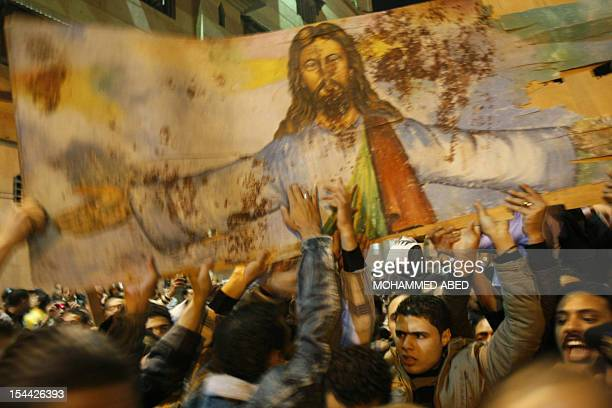 Egyptian Christians hold a blood-stained portrait of Jesus Christ during a protest late on January 2, 2011 outside the Al-Qiddissine church in...