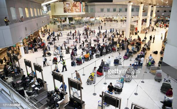 Egyptian citizens queue at Kuwait International Airport before boarding a repatriation flight to Cairo, in Kuwait City on May 5, 2020. - Kuwaiti...