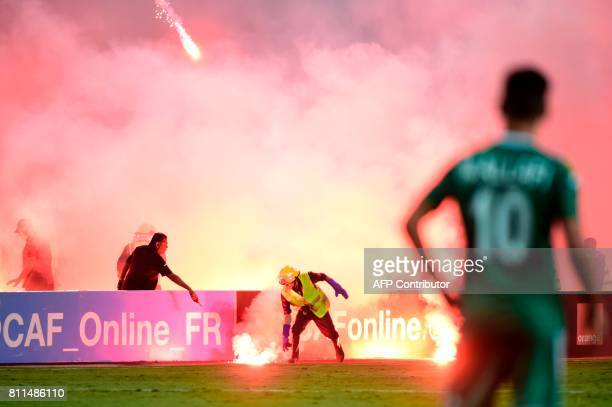 TOPSHOT Egyptian civil defense extinguish flares during the football match between Zamalek and Al Ahly Tripoli during their African Champions League...