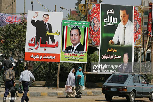 Egyptian civilians walk past electoral posters and billboards promoting Egyptian candidate and current President Hosni Mubarak 06 September 2005 in...