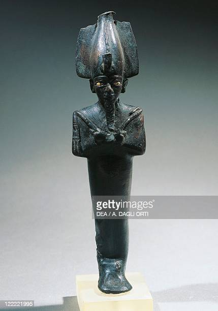 Egyptian civilization Late Period Mummiform figure of Osiris with arms crossed wearing Atef crown Bronze statue h 21 cm