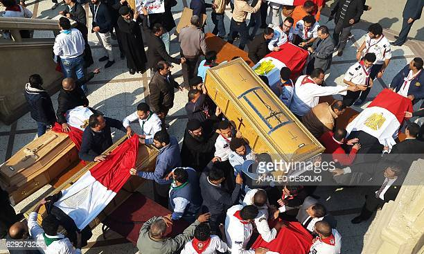 Egyptian clergymen and officials carry the coffins of the victims of a bomb explosion that targeted a Coptic Orthodox Church the previous day in...