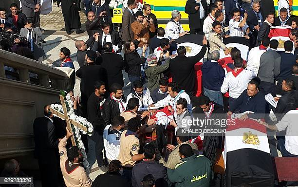 Egyptian clergymen and officials stand next to the coffins of the victims of a bomb explosion that targeted a Coptic Orthodox Church the previous day...