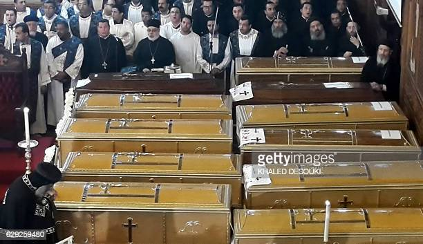 Egyptian clergymen stand next to the coffins of the victims of a bomb explosion that targeted a Coptic Orthodox Church the previous day in Cairo...