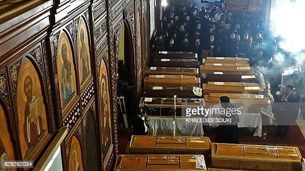TOPSHOT Egyptian clergymen stand next to the coffins of the victims of a bomb explosion that targeted a Coptic Orthodox Church the previous day in...