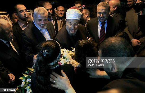Egyptian Cleric and chairman of the International Union of Muslim Scholars Sheikh Yusuf alQaradawi receives flowers from Palestinian girls upon...