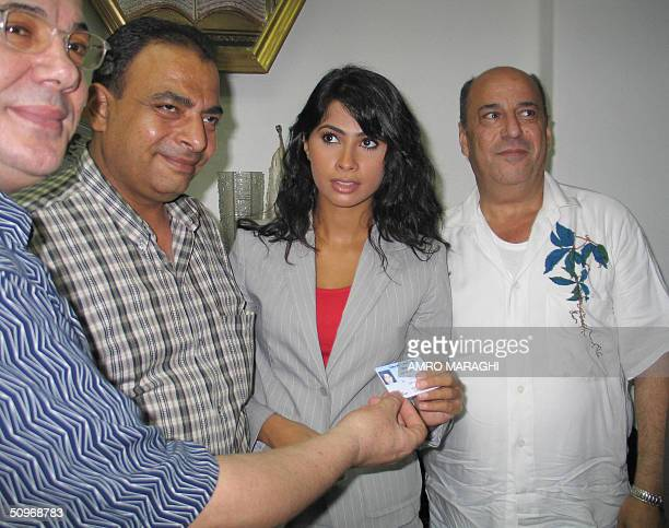 Egyptian composer Gamal Salamah looks on as pop star Ruby receives her membership card in Egypt's musicians union from senior members Hassan Eshesh...