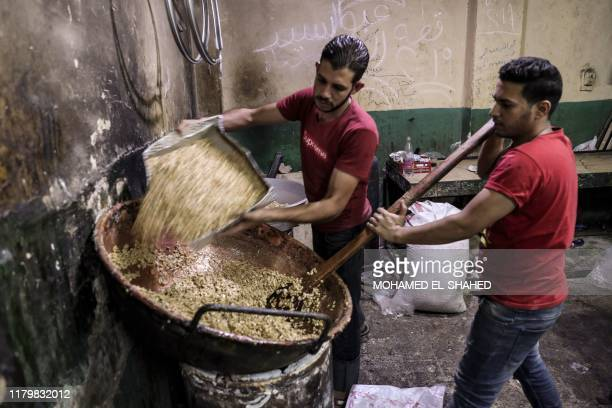 Egyptian confectioners add peanuts to melted sugar as they make sweets at a candy factory in the capital Cairo on November 2 ahead of celebrations of...